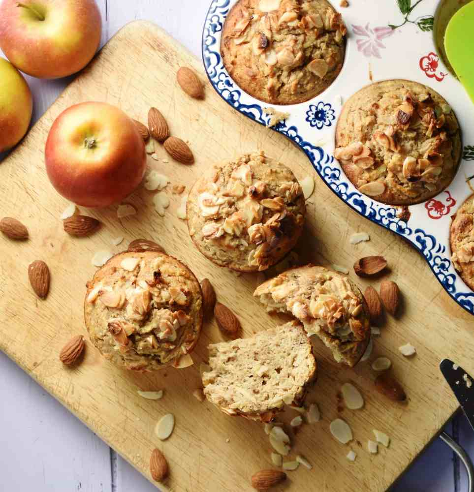 Top down view of muffins, almonds and apples on top of cutting board, with white-and-blue ceramic muffin pan in background.