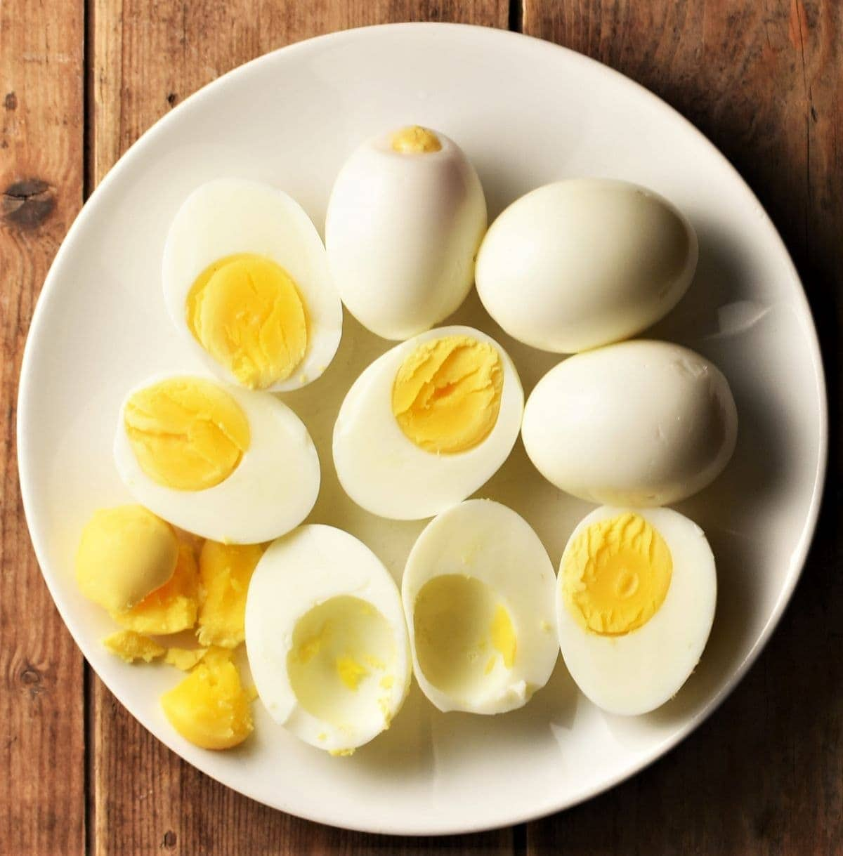 Halved hard boiled eggs on top of white plate.