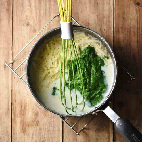 White sauce, pureed spinach and grated cheese in large pot with green whisk.