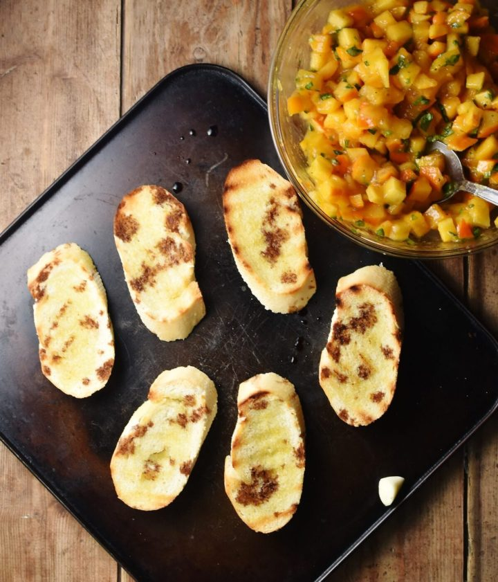 Grilled baguette slices drizzled over with balsamic vinegar on top of black tray, with chopped persimmon mixture in mixing bowl in top right.