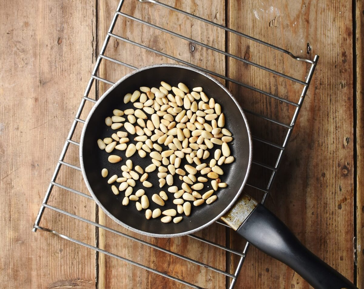 Pine nuts in small pan on rack.