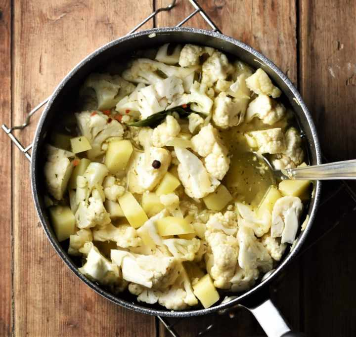 Cubed potato and chopped cauliflower in large pot with spoon.