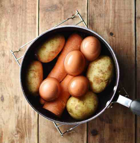 Top down view of unpeeled potatoes, carrots and eggs in large pot with water.