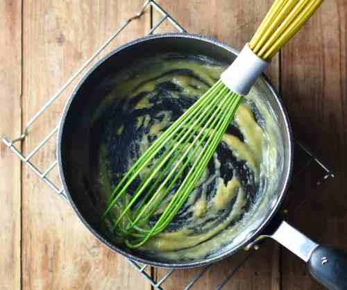 Roux in large pot with green whisk.