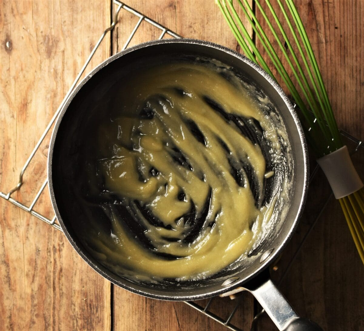 Simple white sauce in black saucepan wrapped in colourful cloth with peppercorns, onion and garlic cloves scattered around.