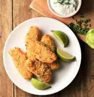Breaded salmon fish fingers on top of plate with lime wedges.