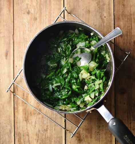 Spinach and onions in large pot with spoon on top of cooling rack.