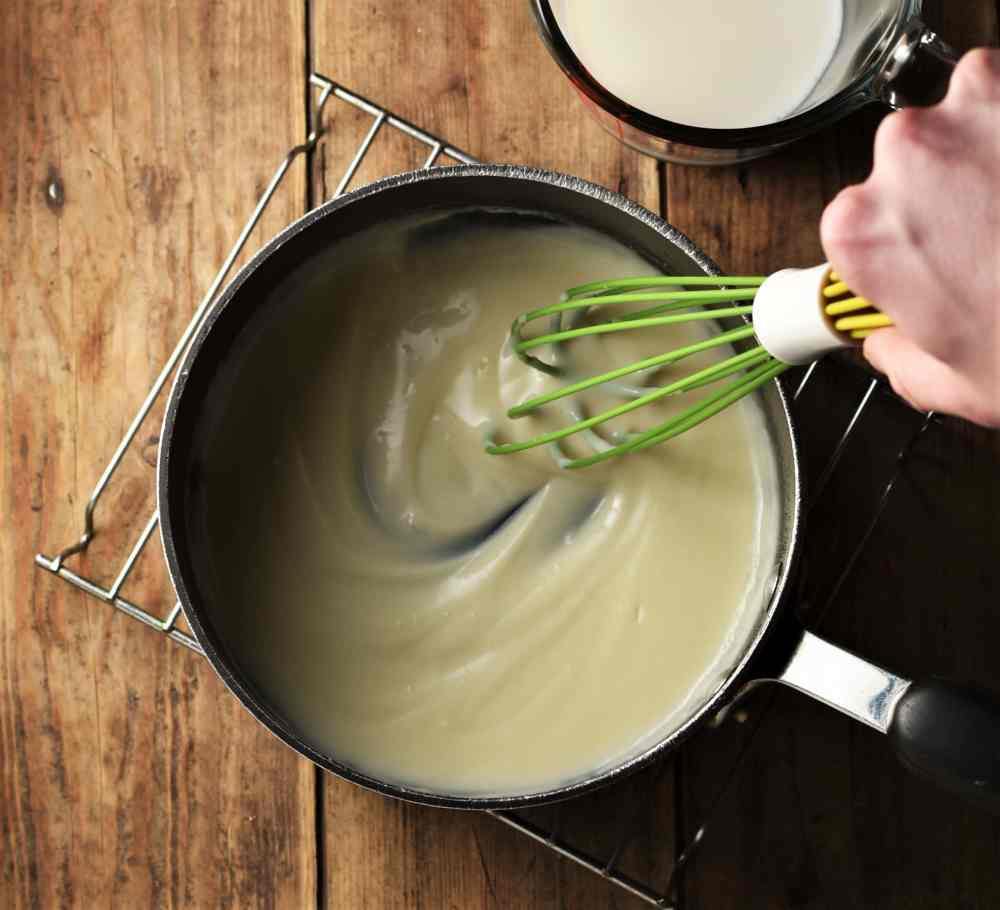Thick white sauce in black pot with hand holding green whisk on top of rack, with milk in dish at the top.