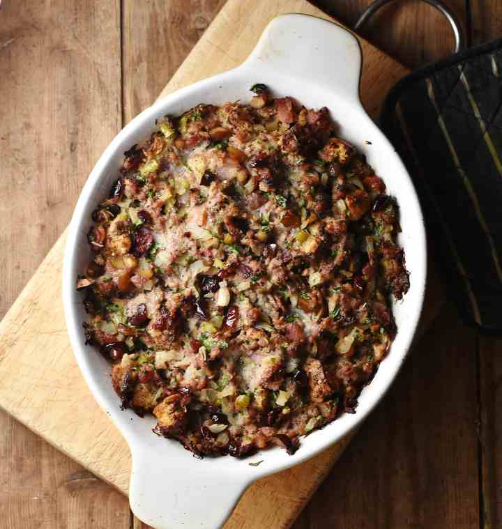 Baked stuffing casserole in white oval dish on top of wooden board.