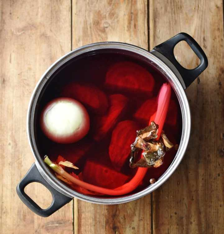 Onion, pieces of beetroot, wild mushrooms and celery stalk in large pot with water.