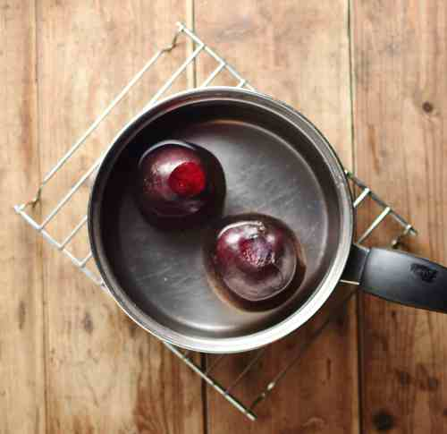 Top down view of 2 beets in water inside saucepan on top of cooling rack.