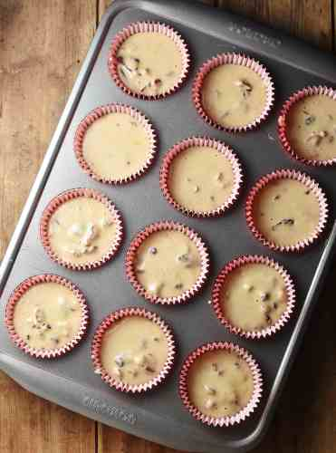 Unbaked cranberry muffins in 12 red paper cases in muffin pan.