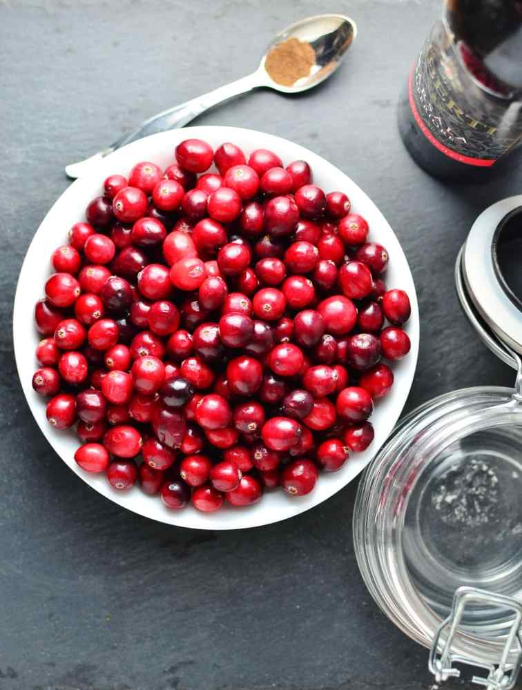 Top down view of raw cranberries inside white bowl, with spoon at top, dark bottle and open jar to the right.