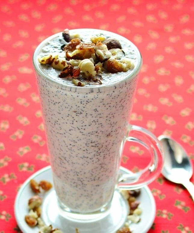 Close-up view of poppy seed raisin overnight oats topped with raisins and nuts in tall glass on top of saucer, with spoon on top of red cloth with hollies pattern.