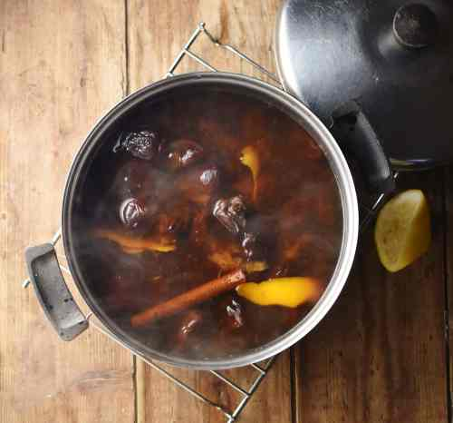 Cooked pruned, orange rind and cinnamon stick and water in pot with steam visible, lemon piece and lid in background.
