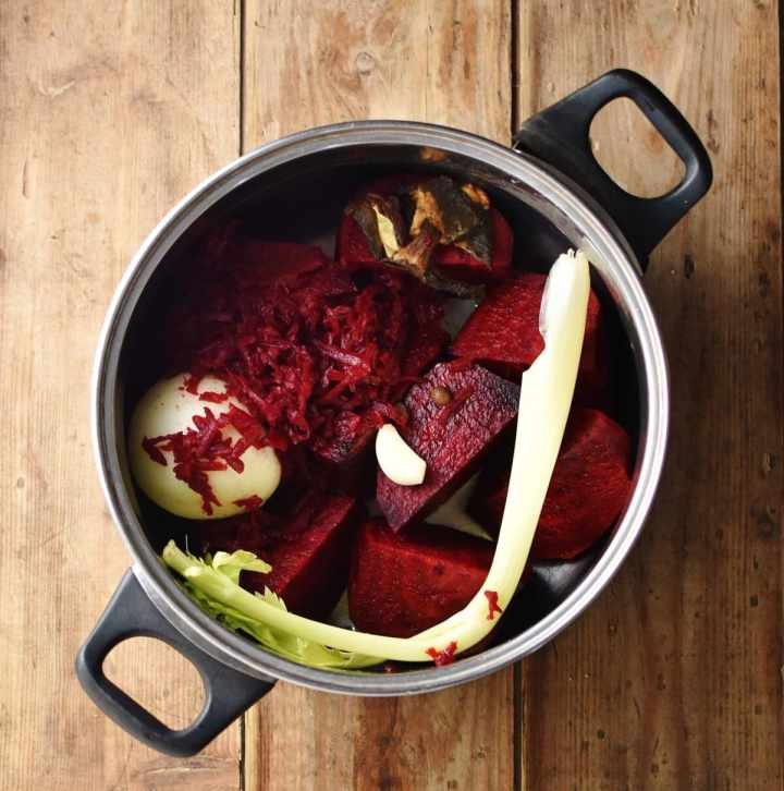 Pieces of beetroot, onion, grated beet, celery, garlic clove and wild mushrooms in large pot.