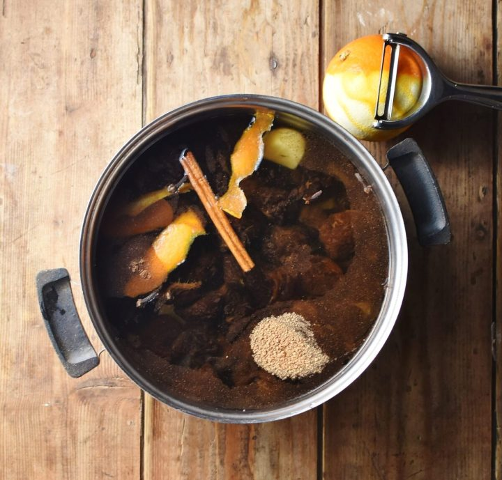 Prunes, orange rind, cinnamon stick and spices with water in pot, with orange and vegetable peeler in background.