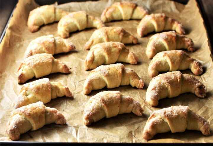 Side view of baked crescent cookies on top of sheet.