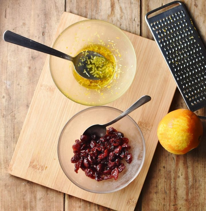Cranberries in bowl with spoon and marinade in another bowl with spoon on top of wooden board, with orange and zester to the right.