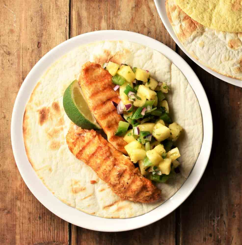 Open tortilla with grilled chicken, pineapple salsa and lime on plate.