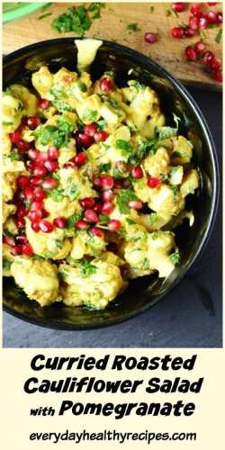 Top down view of curried cauliflower salad with yogurt dressing and pomegranate seeds on top of grey surface.