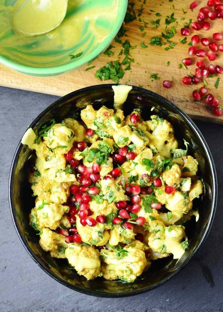 Top down view of curried cauliflower salad with yogurt dressing and pomegranate in black bowl, with green bowl, chopped herbs and pomegranate seeds on top of wooden board.