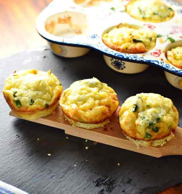 Potato asparagus frittata muffins on wooden board with ceramic muffin tin in background on slate surface.