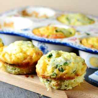 Potato asparagus frittata muffins on wooden board with ceramic muffin tin in background.