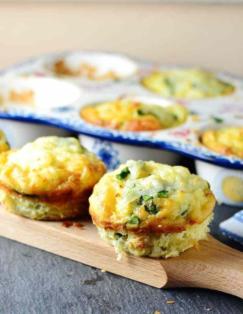 Potato asparagus frittata muffins on wooden board with ceramic muffin tin in background on dark grey surface.
