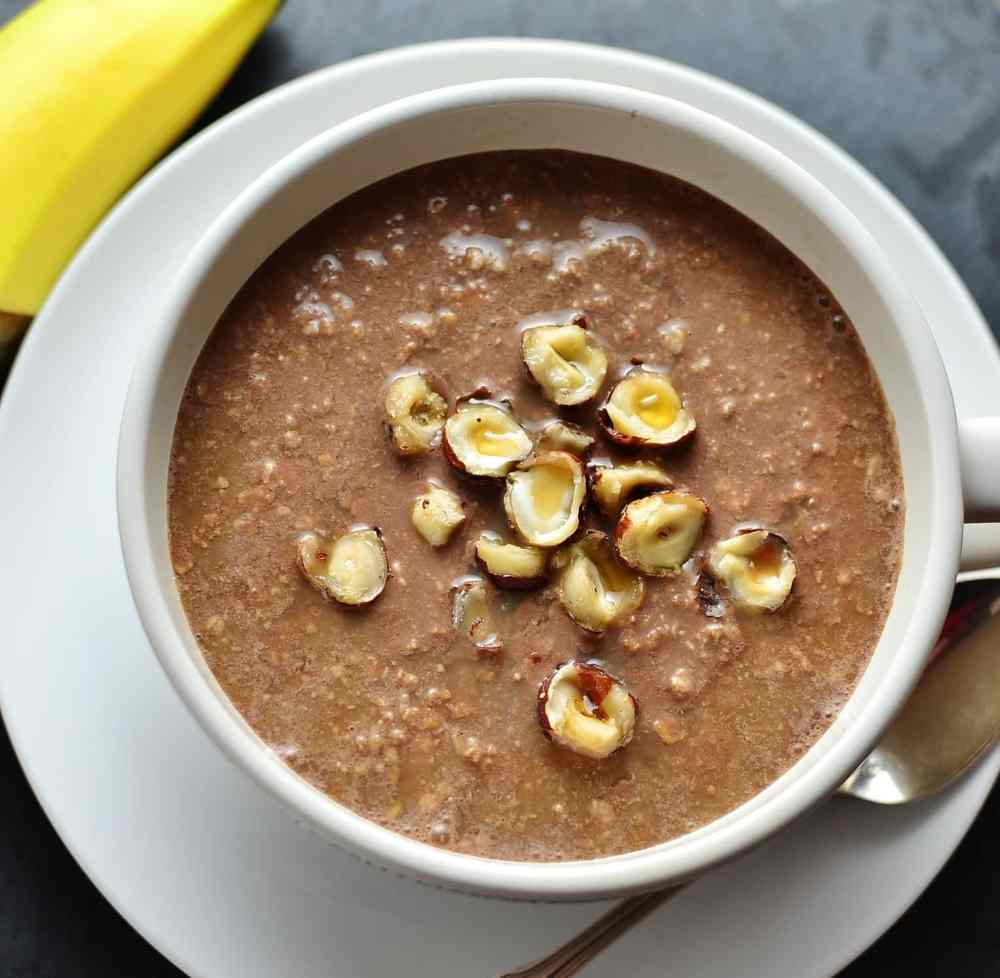 Top down view of chocolate overnight oats topped with crushed hazelnuts in white cup on top of white saucer with spoon and banana in background.