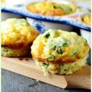 Egg asparagus muffins on wooden board, with white muffin pan with blue pattern in background.