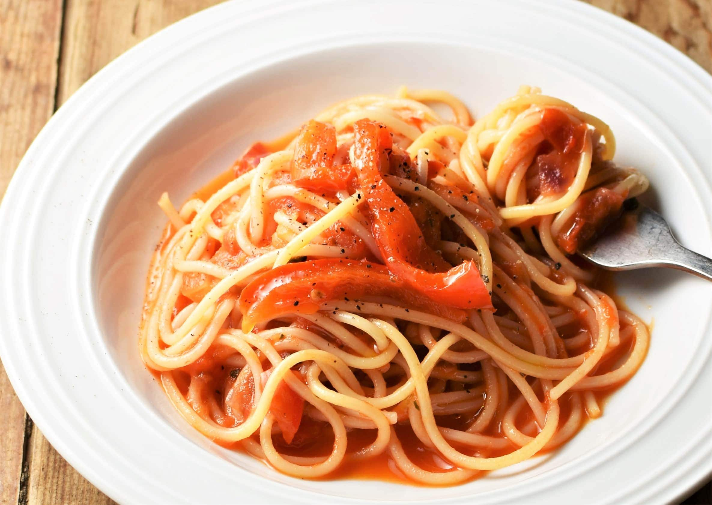 Side view of red pepper pasta with tomato sauce on white plate with fork.