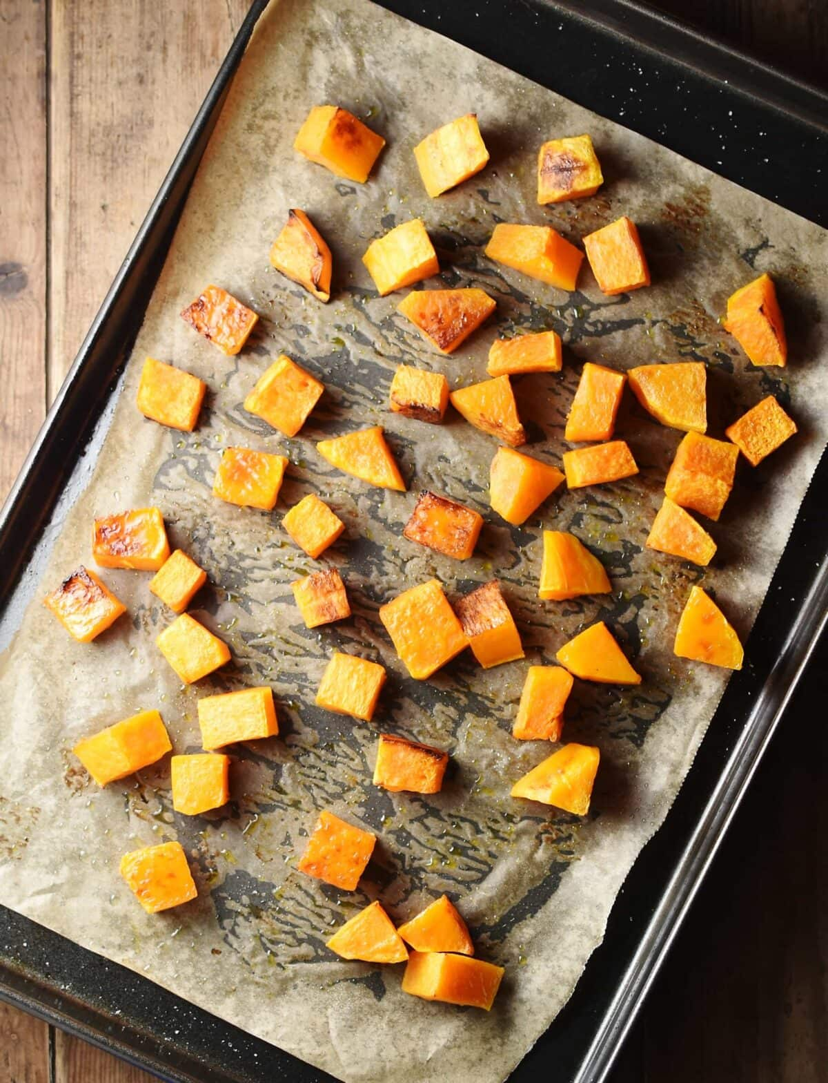 Butternut squash cubes on top of oven tray lined with parchment paper.