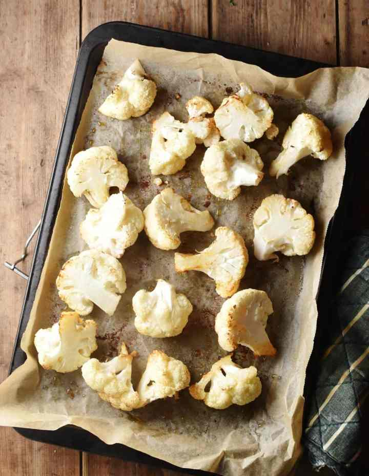 Roasted cauliflower florets on top of baking sheet lined with parchment paper.