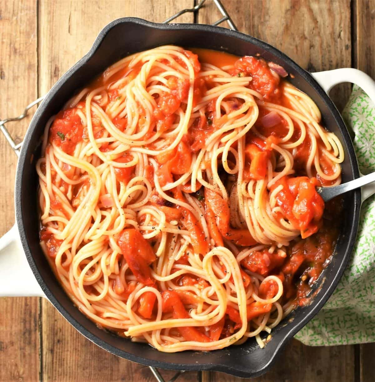 Spaghetti with chunky tomato and red pepper sauce in pan.