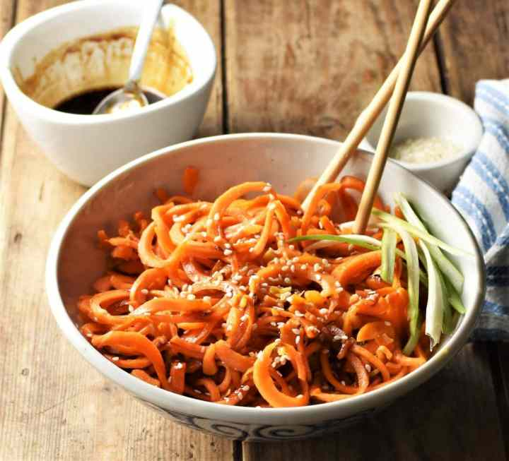 Side view of stir fried spiralized carrot in bowl with chopsticks and glaze in background.