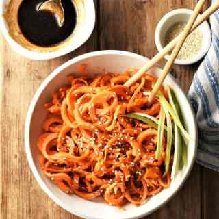 Carrot noodles stir fry in white bowl with chopsticks, seeds and glaze in background.