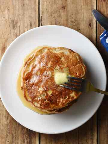 Top down view of pancakes with fork on white plate, and blue patterned cloth with knife in top right corner.