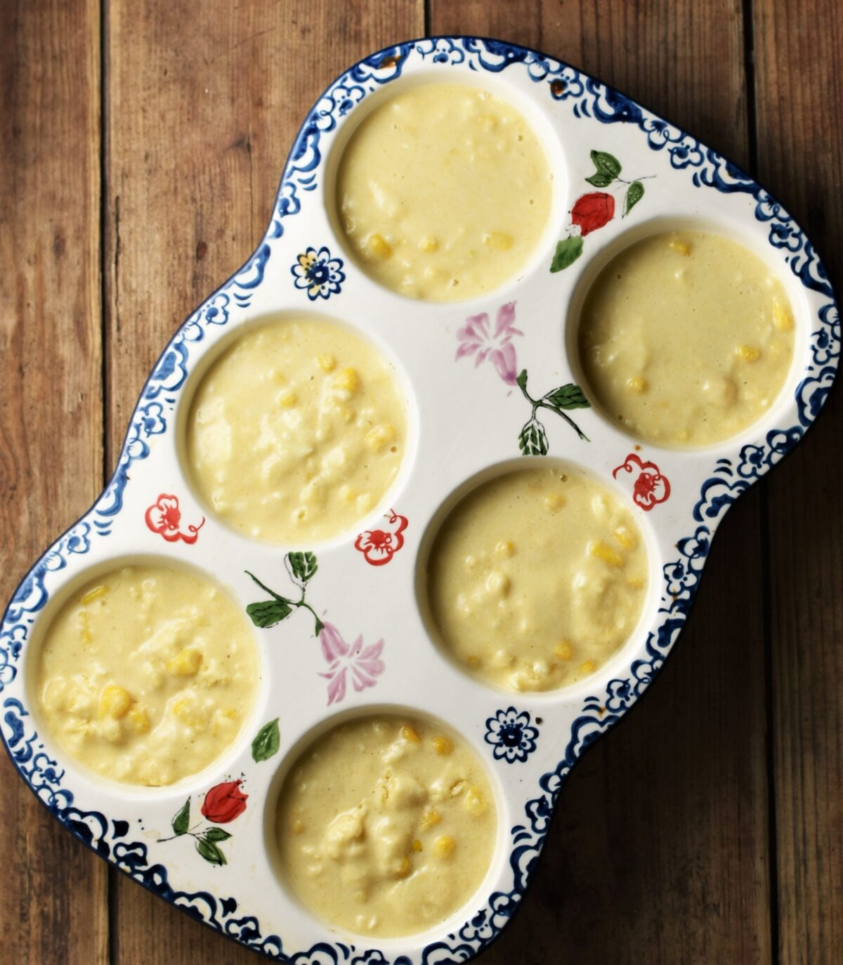 Cornbread muffins batter in ceramic white pan with blue flowery pattern.