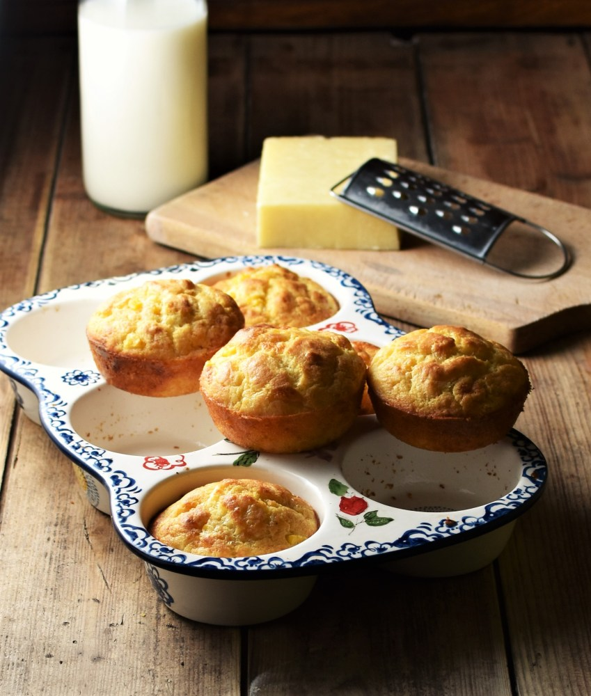 Side view of cornmeal muffins in white ceramic pan with flowery pattern, cheese and grater on top of wooden board and milk in bottle in background.