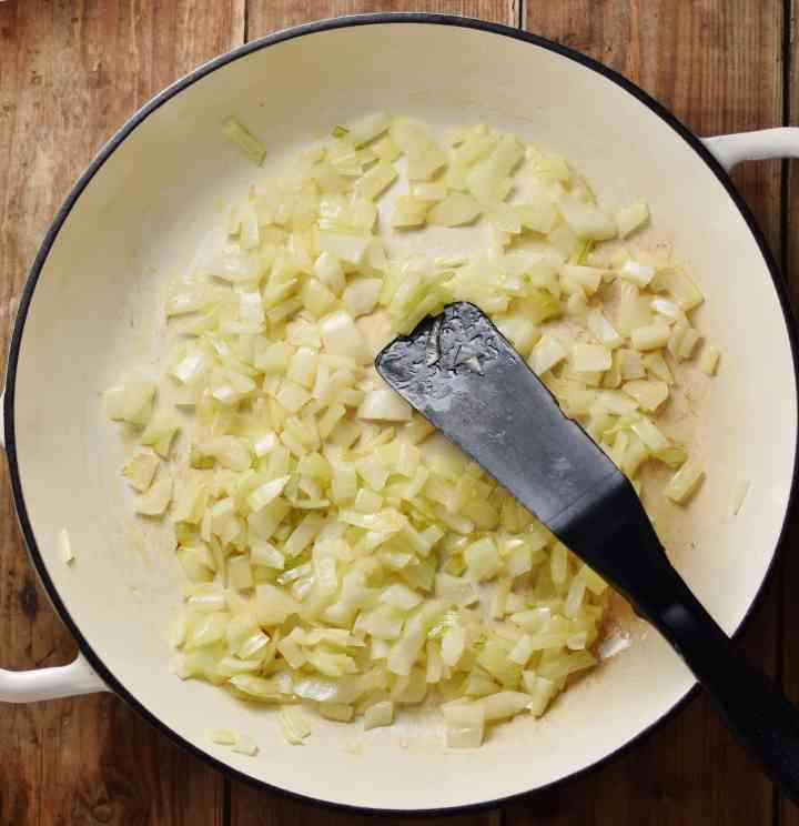 Top down view of onions frying in large shallow white pan with black spatula.