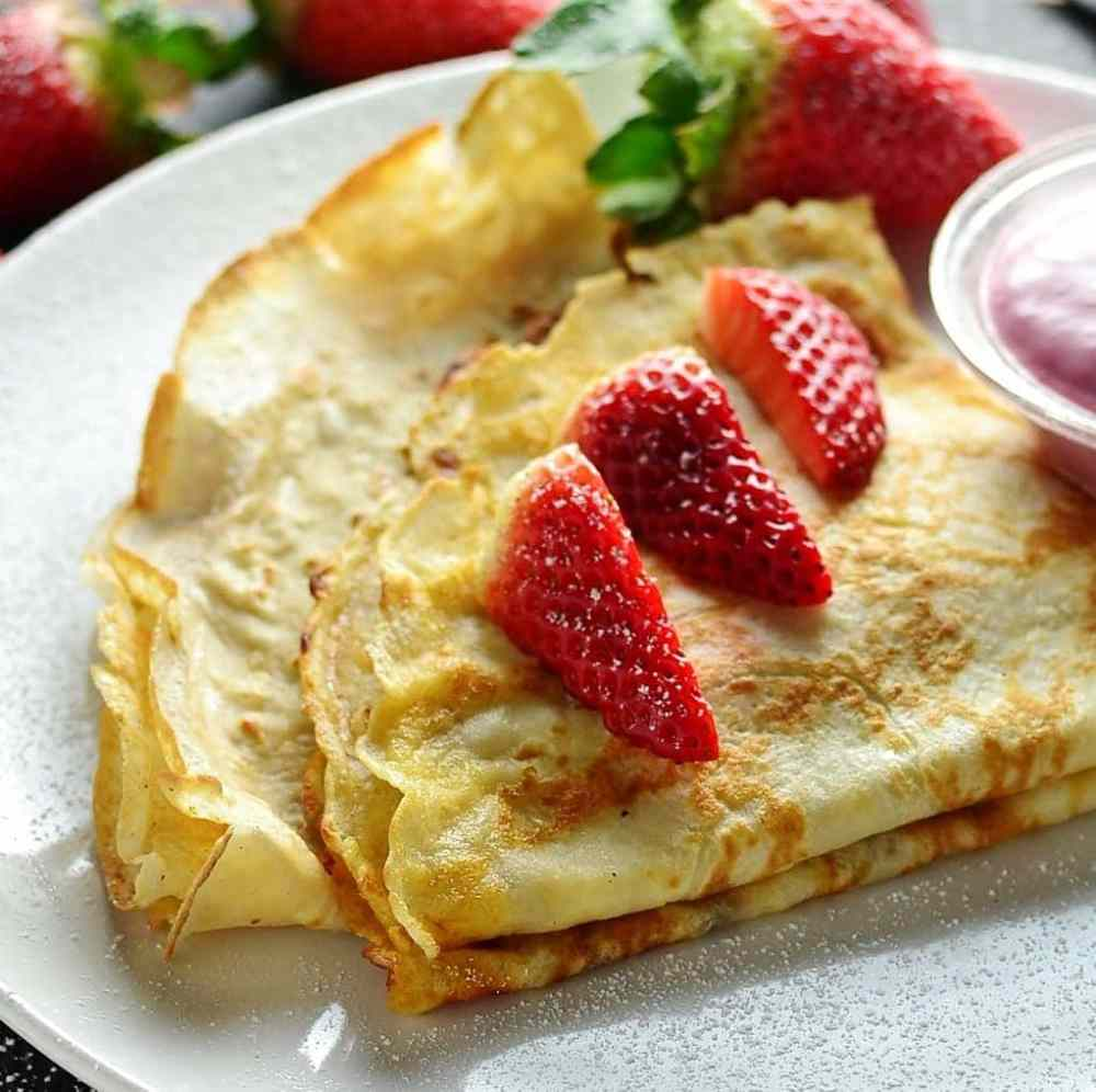 2 folded crepes topped with fresh strawberries on top of white plate.