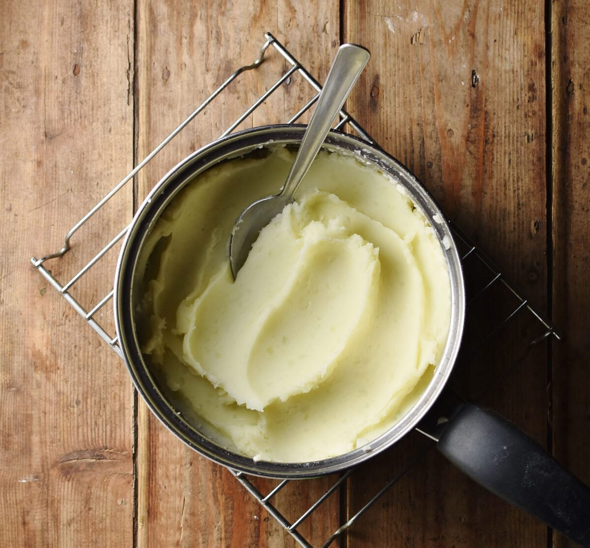 Mashed potatoes with spoon in pot.