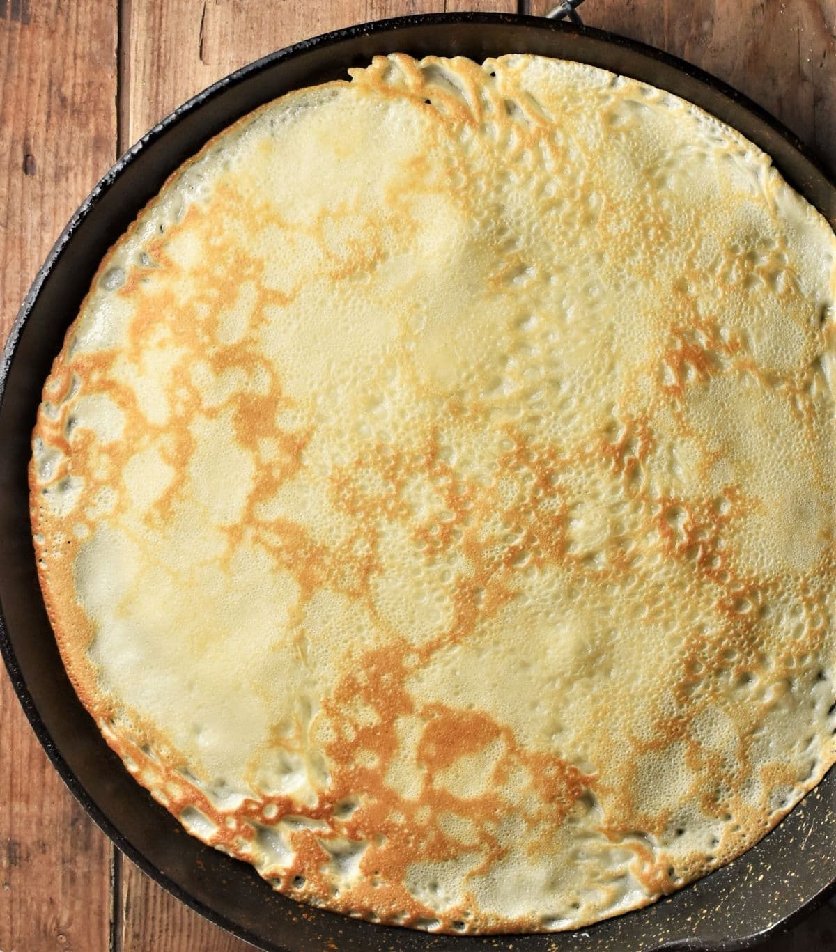 Large crepe on top of frying pan.