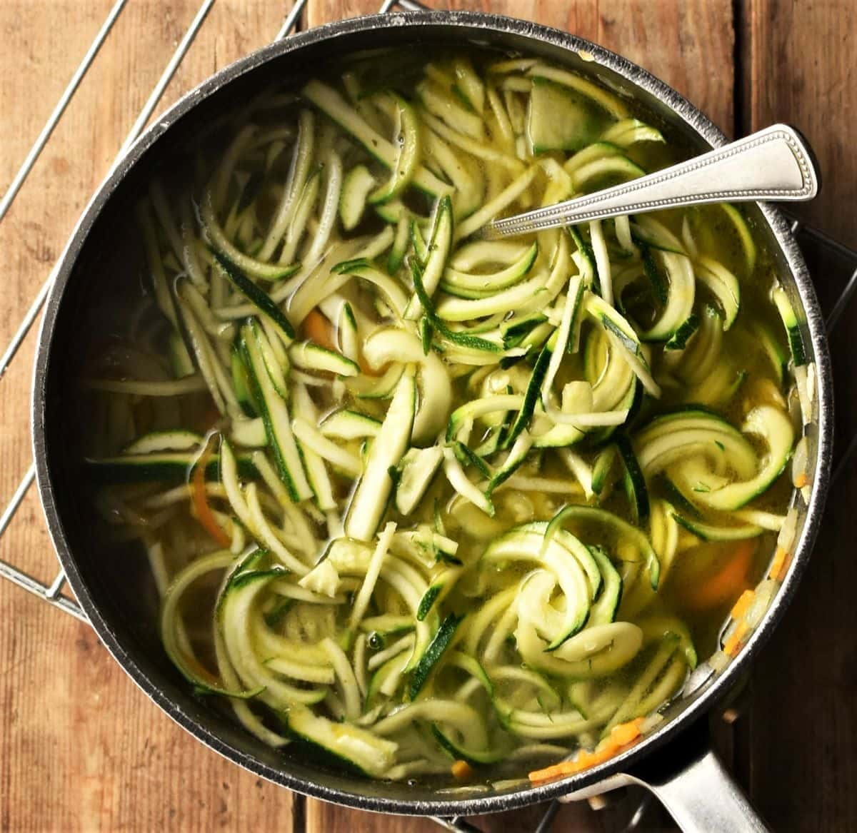 Zucchini noodles in pot with broth and spoon.