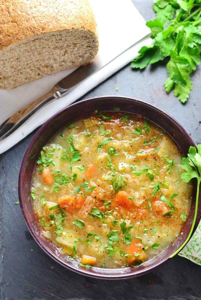 Sauerkraut vegetable kapusniak soup in purple bowl with bread loaf on white cloth with knife and parsley.