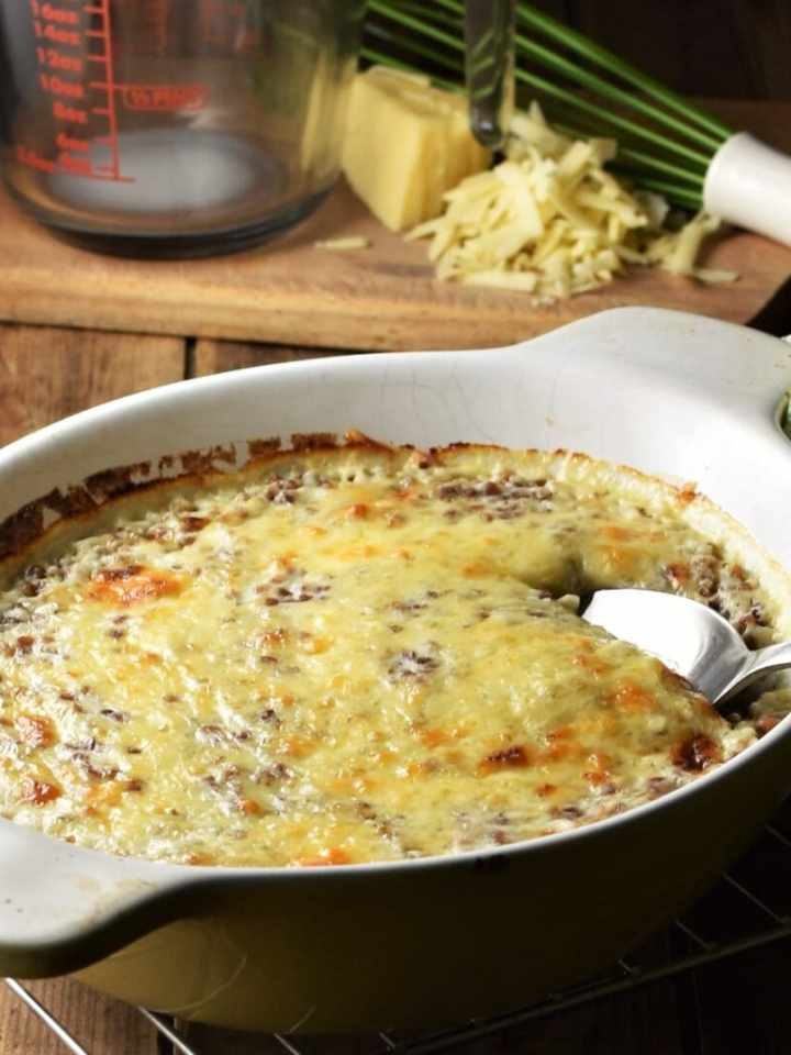 Side view of creamy buckwheat topped with melted cheese in white dish with spoon, green cloth, whisk, grated cheese and measuring cup in background.