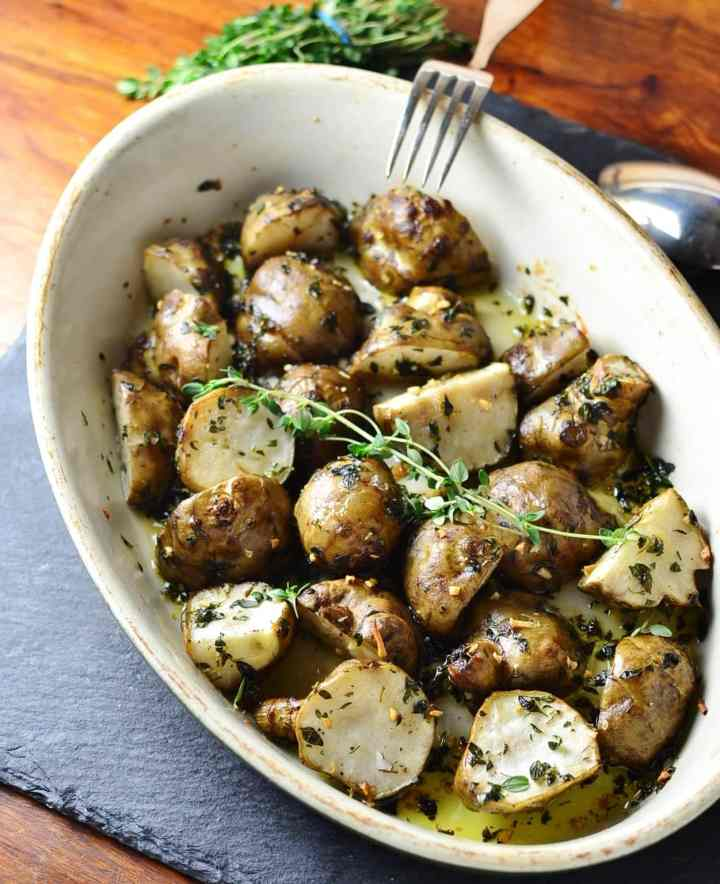 Top down view of roasted Jerusalem artichokes with herbs in white oval dish with spoon, fork and fresh herbs on dark grey table.