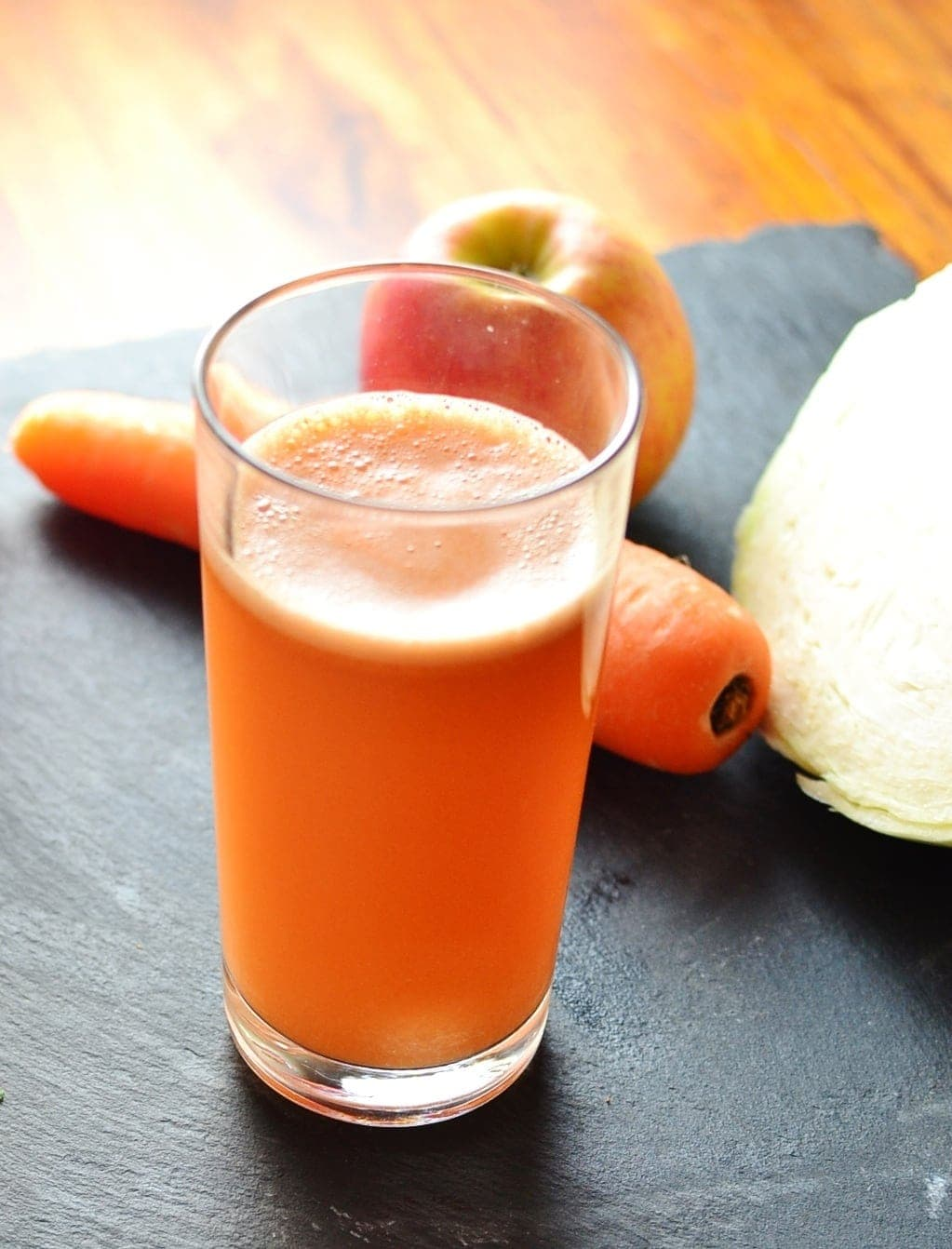 Cabbage juice in glass with carrot and apple on slate surface.
