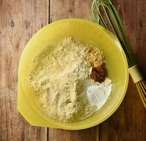 Flour and spice in large yellow bowl with green whisk.